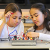 Emily Allen , 10, left, and Catherine Carmosino, 9, work on properly wiring the board for an experiment during the Electronic Lab taught by Fred Gluck of CU Science Discovery at Mamie Doud Eisenhower Public Library on Saturday.<br /> February 16, 2013<br /> staff photo/ David R. Jennings