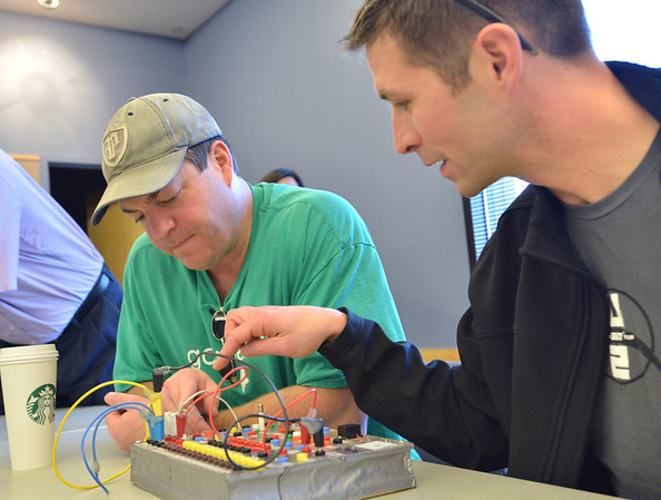 Parents Scott Trathen, left, and Joe Allen try to figure out how to wire a series to light three  LED bulbs on the circuit board using only four wires during the Electronic Lab taught by Fred Gluck of CU Science Discovery at Mamie Doud Eisenhower Public Library on Saturday.<br /> February 16, 2013<br /> staff photo/ David R. Jennings