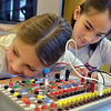 Emily Allen, 10, left,  with Catherine Carmosino, 9, listens for a slight tone from a buzzer during the Electronic Lab taught by Fred Gluck of CU Science Discovery at Mamie Doud Eisenhower Public Library on Saturday.<br /> staff photo/ David R. Jennings