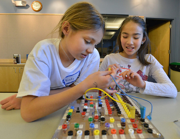 Emily Allen, 10, left, and Catherine Carmosino, 9, try to figure out how to correctly wire a switch on the board during the Electronic Lab taught by Fred Gluck of CU Science Discovery at Mamie Doud Eisenhower Public Library on Saturday.<br /> February 16, 2013<br /> staff photo/ David R. Jennings