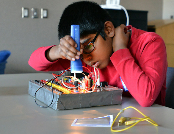 Kokila Gunasinghe, 9, uses a flashlight to trigger a photo sensor during the Electronic Lab taught by Fred Gluck of CU Science Discovery at Mamie Doud Eisenhower Public Library on Saturday.<br /> February 16, 2013<br /> staff photo/ David R. Jennings