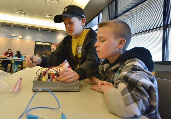 Brothers Blake Steinmetz, 10, left, and Dante, 12, move wires on their board to make an LED lite during the Electronic Lab taught by Fred Gluck of CU Science Discovery at Mamie Doud Eisenhower Public Library on Saturday.<br /> February 16, 2013<br /> staff photo/ David R. Jennings