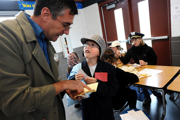 ELLIS03<br /> Ethan Weil, right, struggles to understand the foreign language spoken by Dan DeGolier, a parent volunteer, as his paperwork is inspected during an Ellis Island re-enactment at Crest View Elementary School on Monday. <br /> Photo by Marty Caivano/Camera/May 10, 2010