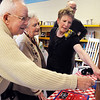 Retiring teacher Cindy Stricker, right, shows her parents Bob and Ottilie Seeber her poster staff made during Friday's retirement party at Emerald Elementary School. Stricker also was a student at Emerald.<br /> May 7, 2010<br /> Staff photo/ David R. Jennings