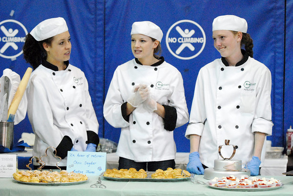 Broomfield High Pro Start students Kelly Baum, left, Desire Warner, and Abby Carlson wait for guests to be served at the table dedicated to retiring teacher Chris Snyder during Friday's retirement party at Emerald Elementary School. The Pro Start students prepared food with table honoring each retiree.<br /> May 7, 2010<br /> Staff photo/ David R. Jennings