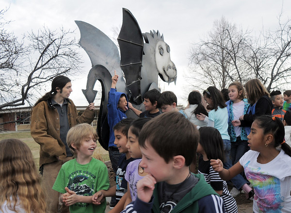 Students of Emerald Elementary School move around after they were photographed with the steel sculpture of the school's mascot, Snortner, with artist Chapin Diamond after the dedication on Thursday. <br /> March 31, 2011<br /> staff photo/David R. Jennings