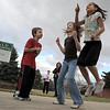 Third grader Nathan Cote, left, Toree Seratt, 5th grade, and Maya Mowery-Evans, third grade, jump to keep warm during the Emerald Elementary School dedication of the sculpture of Snortner, the school's mascot, on Thursday. <br /> <br /> March 31, 2011<br /> staff photo/David R. Jennings