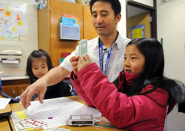Angie Pan, 8, right, adds numbers on cards while playing a math game with her father Alex and her sister Olivia, 2, in a second grade classroom during Emerald Elementary School's Family Math Night Tuesday. 195 parents and students showed for the event an increase from a mere 8 about three years ago.<br /> <br /> November 17, 2009<br /> Staff photo/David R. Jennings