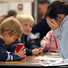 Kristin Berry, right, hides her eyes while her son, Isaac, 6, divides beans for her to guess the number during Emerald Elementary School's Family Math Night in a first grade classroom on Tuesday. 195 parents and students showed for the event an increase from a mere 8 about three years ago said principal Larry Leatherman.<br /> <br /> November 17, 2009<br /> Staff photo/David R. Jennings