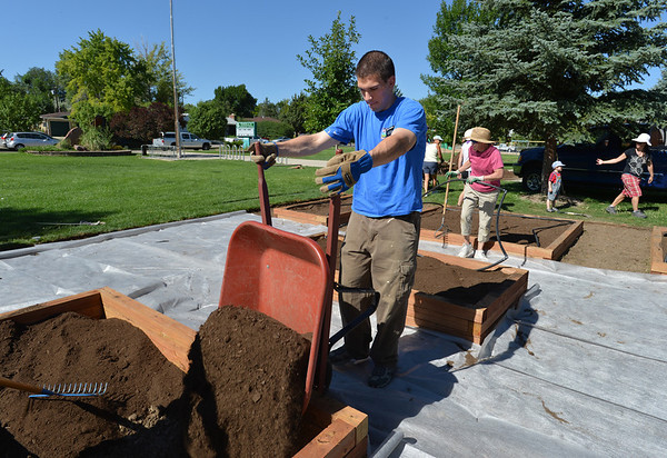 Alex Washburn dumps a wheelbarrow of dirt into a raised frame while  working on the new garden at Emerald Elementary School on Saturday.<br /> <br /> July 21, 2012<br /> staff photo/ David R. Jennings