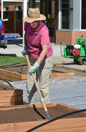 Lynne O'Hara rakes soil in a raised bed for the new garden at Emerald Elementary School on Saturday.<br /> <br /> July 21, 2012<br /> staff photo/ David R. Jennings