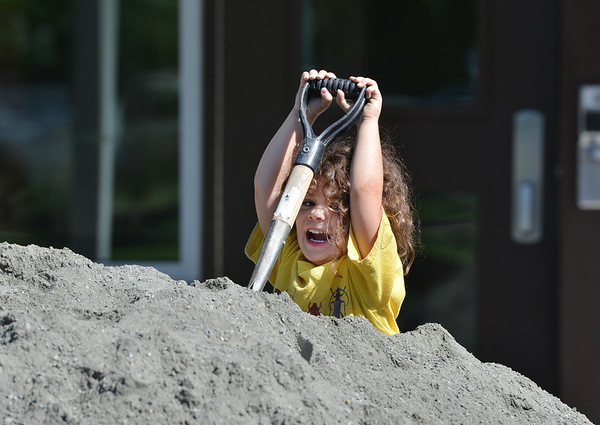 Vivenne Crutcher, 4, tries to use a shovel while helping load wheelbarrows with gravel for the new garden at Emerald Elementary School on Saturday.<br /> <br /> July 21, 2012<br /> staff photo/ David R. Jennings