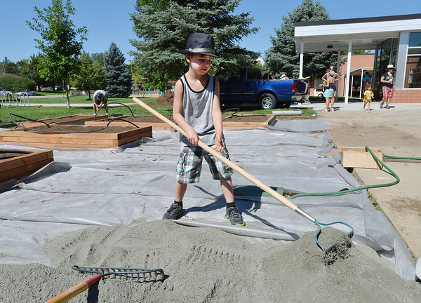 Liam Lenihan, 7, rakes gravel in the new garden at Emerald Elementary School on Saturday.<br /> <br /> July 21, 2012<br /> staff photo/ David R. Jennings