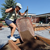 Geri Irvin dumps a wheelbarrow of dirt into a raised frame while  working on the new garden at Emerald Elementary School on Saturday.<br /> <br /> <br /> July 21, 2012<br /> staff photo/ David R. Jennings