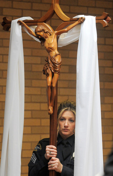 Officer Enea Hempelmann holds a cross in the procession during the funeral of  Broomfield Police detective Bruce Fitzgerald at Spirit of Christ Church in Arvada on Thursday.<br /> May 12, 2011<br /> staff photo/David R. Jennings