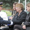 Police Chief Tom Deland, left, gives the flag to Jane Fitzgerald, right, center, and daughters Meghan Fitzgerald-Brown and Erin Fitzgerald during the funeral for Broomfield Police Detective Bruce Fitzgerald at Spirit of Christ Church in Arvada on Thursday.<br /> May 12, 2011<br /> staff photo/David R. Jennings