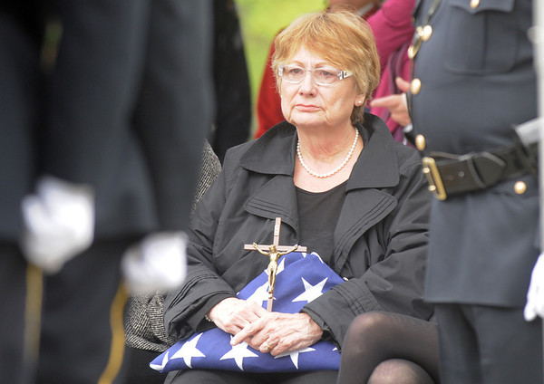 Jane Fitzgerald holds the flag and crass for her husband Broomfield Police Detective Bruce Fitzgerald during the funeral for at Spirit of Christ Church in Arvada on Thursday.<br /> May 12, 2011<br /> staff photo/David R. Jennings