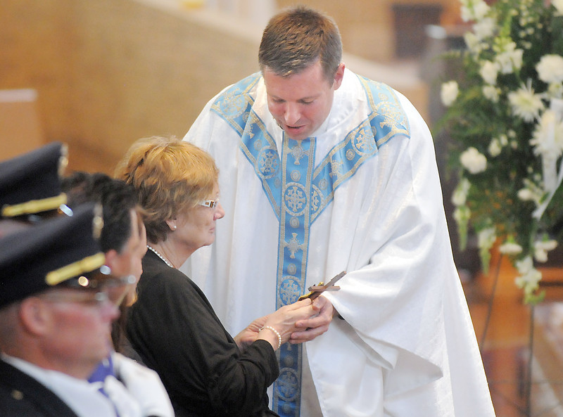 Father Matthew Book gives a cross to Jane Fitzgerald in honor of her husband Broomfield Police detective Bruce Fitzgerald during the funeral at Spirit of Christ Church in Arvada on Thursday.<br /> May 12, 2011<br /> staff photo/David R. Jennings
