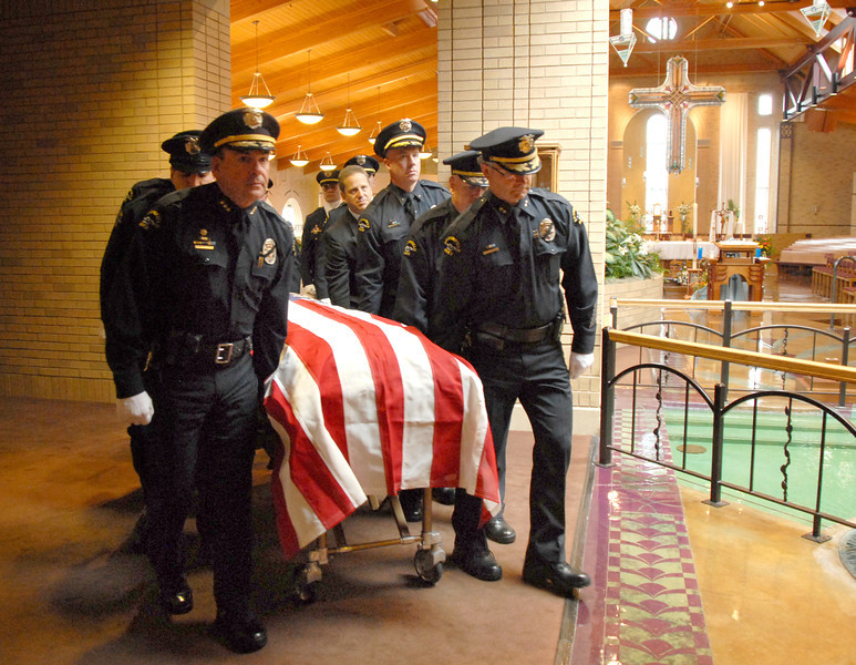 Pallbears lead by Chief Tom Deland, left, and Deputy Chief Jim Pfankuch, right, carry the casket of Broomfield Police detective Bruce Fitzgerald during his funeral at Spirit of Christ Church in Arvada on Thursday.<br /> May 12, 2011<br /> staff photo/David R. Jennings