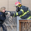 Broomfield Police commander Linda Haines takes a dog from North Metro Fire Rescue Capt. Rich Randall rescued by firefighters at a house fire at 308 Mulberry Circle.<br /> No reports of injuries the cause of the fire  is under investigation.<br /> March 6, 2010<br /> Staff photo/David R. Jennings