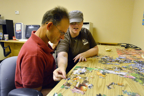 Bob Grizmala, left, has help with a jigsaw puzzle from F.R.I.E.N.D.S. of Broomfield staff member Rose Means in a multipurpose room on Friday.  F.R.I.E.N.D.S. is breaking ground on a new center this week.<br /> May 25, 2012 <br /> staff photo/ David R. Jennings