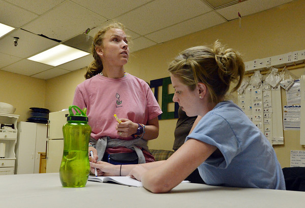 F.R.I.E.N.D.S. of Broomfield staff member Lynn Ersek, right, works with Sarah Miller on a writing project in a multipurpose room on Friday.  F.R.I.E.N.D.S. is breaking ground on a new center this week.<br /> May 25, 2012 <br /> staff photo/ David R. Jennings