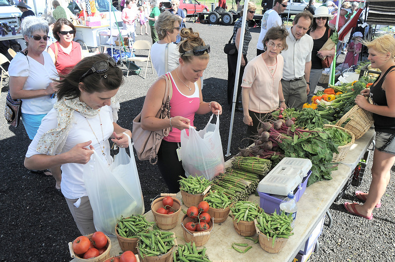 Customers choose their vegetables at the Miller Farms booth during the first Farmers Market at Holy Comforter Church on Tuesday.<br /> June 14, 2011<br /> staff photo/David R. Jennings