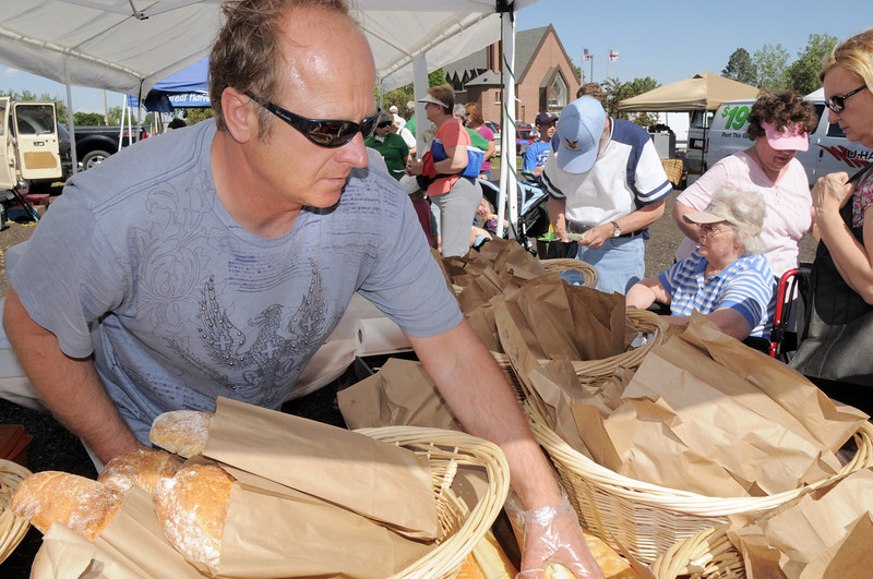 Will Kogler with Fresh Breads and Pastries, grabs a loaf for a customer during the first Farmers Market at Holy Comforter Church on Tuesday.<br /> June 14, 2011<br /> staff photo/David R. Jennings