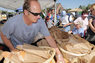 Will Kogler with Fresh Breads and Pastries, grabs a loaf for a customer during the first Farmers Market at Holy Comforter Church on Tuesday. June 14, 2011 staff photo/David R. Jennings