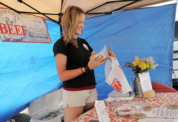 Kelsa Erickson with Colorado's Best Beef, puts frozen beef in a bag for a customer during the first Farmers Market at Holy Comforter Church on Tuesday.<br /> June 14, 2011<br /> staff photo/David R. Jennings