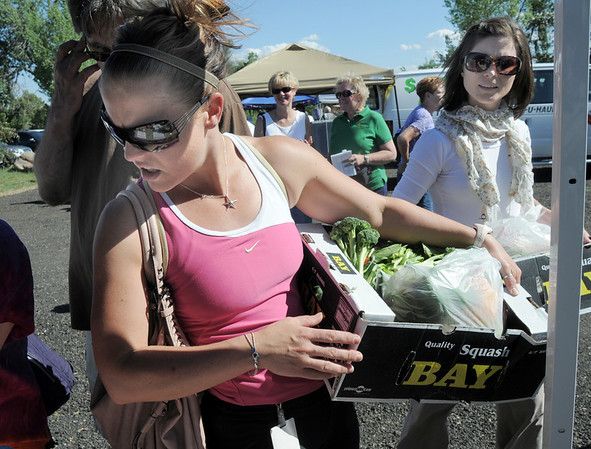 Sara Baker, left, and Lori Duncan carry vegetables while shopping at other booths during the first Farmers Market at Holy Comforter Church on Tuesday.<br /> June 14, 2011<br /> staff photo/David R. Jennings
