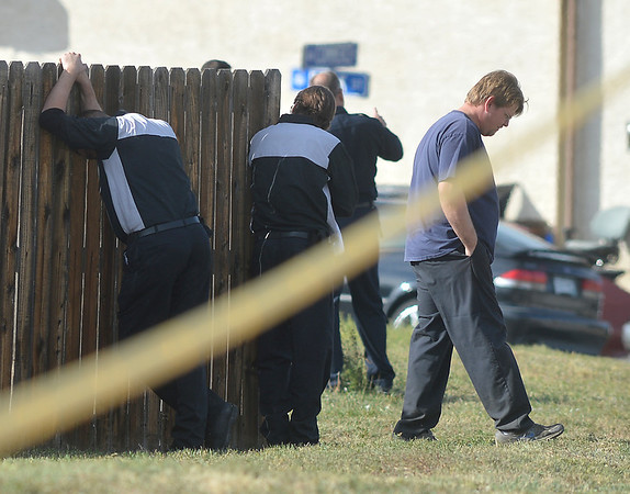 Possible employees of East of Sweden stand near a fence at 155 Commerce St. where a fatal shooting took place on Friday in Broomfield.<br /> October 12, 2012<br /> staff photo/ David R. Jennings