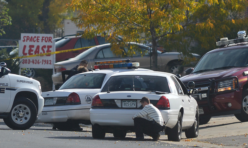 A detective takes notes behind a car at 155 Commerce St. where a shooting took place on Friday in Broomfield.<br /> October 12, 2012<br /> staff photo/ David R. Jennings