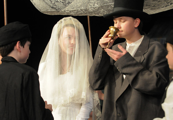 Grant Holman, Motel, left, takes a drink as Kali Zack, Tzeitel, looks on during the wedding ceremony with Bryce Gordon, the Rabbi, right, for the rehearsal of  Broomfield Heights Middle School production of Fiddler on the Roof on Thursday.<br /> <br /> March 15,  2012 <br /> staff photo/ David R. Jennings