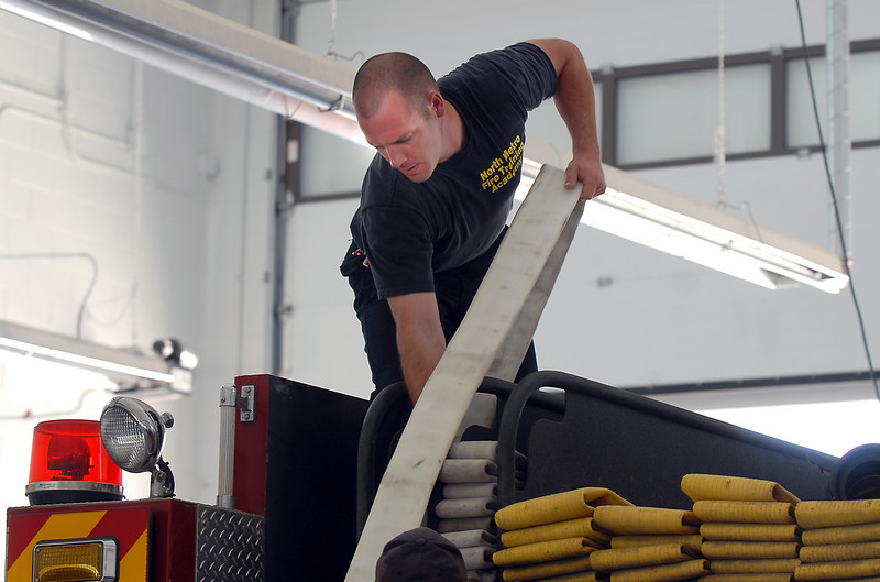 Trainee Matt Olig works on placing fire hose in an engine during evaluation day for the first class to complete their 16-week training at the North Metro Fire Rescue District Training Center on Friday.<br /> July 9, 2010<br /> Staff photo/ David R. Jennings