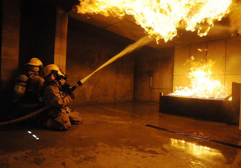 Fire trainees Adam Van Volkinburg, right, and Ryan Ziccarelli use a fast attack to fight a live burn basement fire during testing day for the first class to complete their 16-week training at the North Metro Fire Rescue District Training Center on Friday.<br /> July 9, 2010<br /> Staff photo/ David R. Jennings