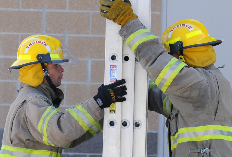 Fire trainees Caleb Larson, left, and Adam Van Volkinburg go through their ladder test during evaluation day for the first class to complete their 16-week training at the North Metro Fire Rescue District Training Center on Friday.<br /> <br /> July 9, 2010<br /> Staff photo/ David R. Jennings