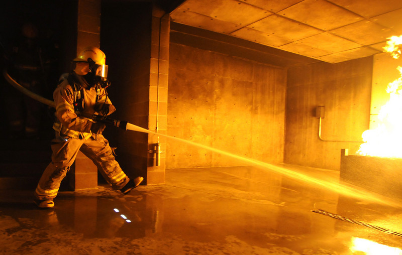 BE0711FIRE09<br /> Fire trainee Adam Van Volkinburg use a fast attack to fight a live burn basement fire during testing day for the first class to complete their 16-week training at the North Metro Fire Rescue District Training Center on Friday.<br /> <br /> July 9, 2010<br /> Staff photo/ David R. Jennings