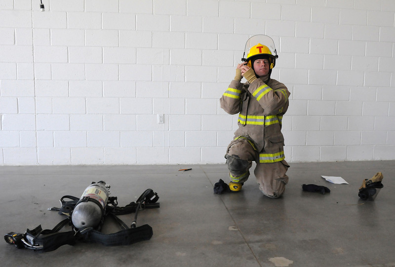 Fire trainee Shane Dougherty takes the timed test for puting on his fire gear during testing day for the first class to complete their 16-week training at the North Metro Fire Rescue District Training Center on Friday.<br /> <br /> July 9, 2010<br /> Staff photo/ David R. Jennings
