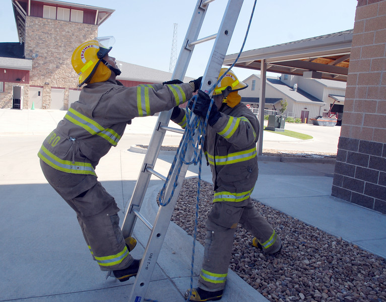 Trainees Caleb Larson, left, and Ryan Ziccarelli perform a ladder test  during evaluation day for the first class to complete their 16-week training at the North Metro Fire Rescue District Training Center on Friday.<br /> July 9, 2010<br /> Staff photo/ David R. Jennings