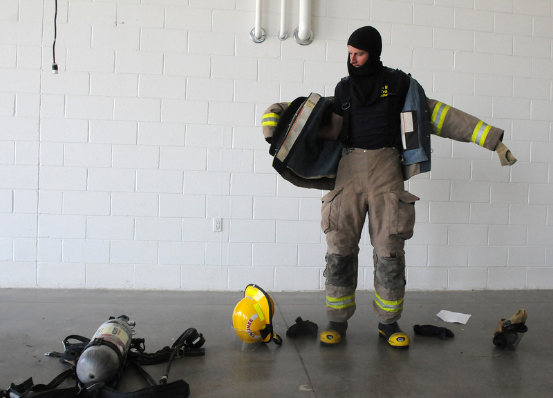 Trainee Shane Dougherty puts on his gear in a timed test on evaluation day for the first class to complete their 16-week training at the North Metro Fire Rescue District Training Center on Friday.<br /> July 9, 2010<br /> Staff photo/ David R. Jennings