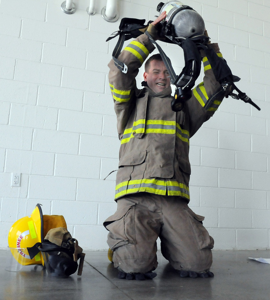 Fire trainee Shane Dougherty puts on his airpack during testing day for the first class to complete their 16-week training at the North Metro Fire Rescue District Training Center on Friday.<br /> <br /> July 9, 2010<br /> Staff photo/ David R. Jennings