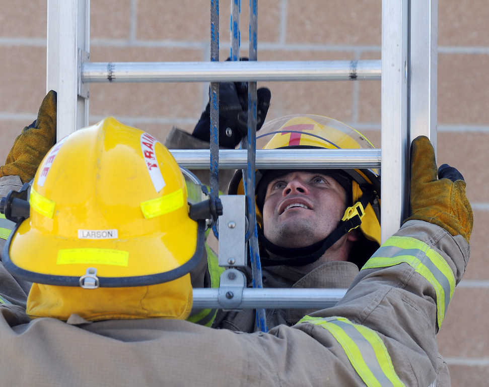 Trainee Ryan Ziccarelli, right, raises a ladder held by Caleb Larson during testing day for the first class to complete their 16-week training at the North Metro Fire Rescue District Training Center on Friday.<br /> July 9, 2010<br /> Staff photo/ David R. Jennings