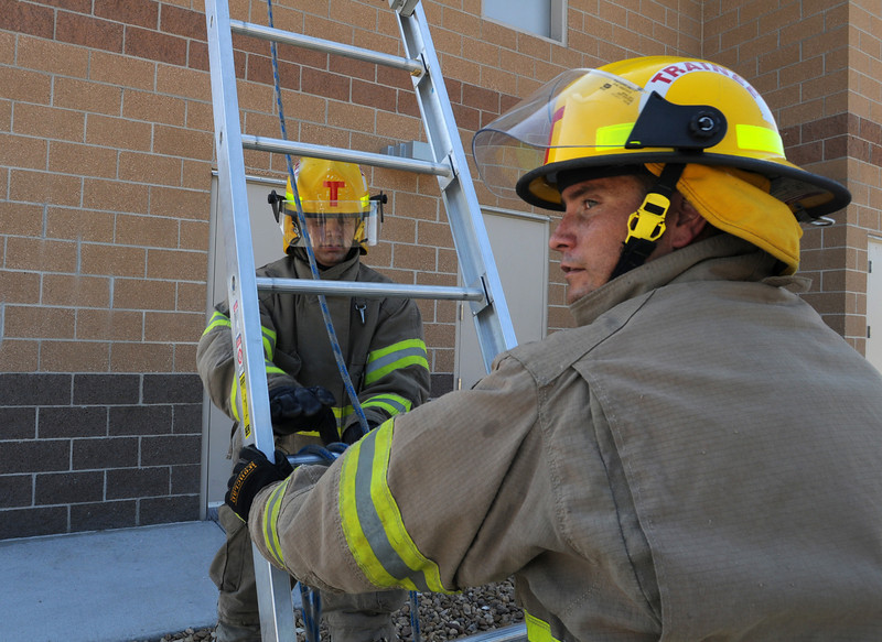 BE0711FIRE12<br /> Fire trainees Adam Van Volkinburg, left, and Caleb Larson set a ladder on a tall building during testing day for the first class to complete their 16-week training at the North Metro Fire Rescue District Training Center on Friday.<br /> <br /> July 9, 2010<br /> Staff photo/ David R. Jennings
