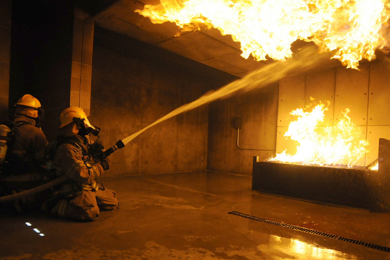 Fire trainees Adam Van Volkinburg and Ryan Ziccarelli sprays the ceiling during fast attack on a live burn basement fire during evaluation day for the first class to complete their 16-week training at the North Metro Fire Rescue District Training Center on Friday.<br /> <br /> July 9, 2010<br /> Staff photo/ David R. Jennings