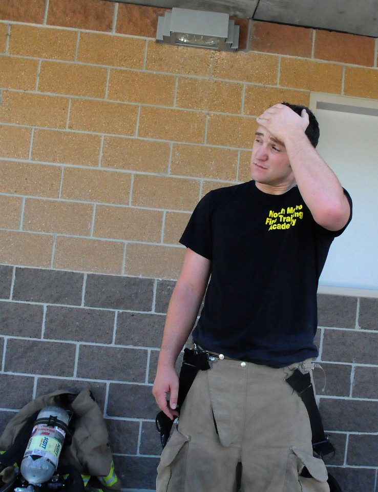 Fire trainee Caleb Larson wipes his brow after a  a live burn basement fire during testing day for the first class to complete their 16-week training at the North Metro Fire Rescue District Training Center on Friday.<br /> <br /> July 9, 2010<br /> Staff photo/ David R. Jennings