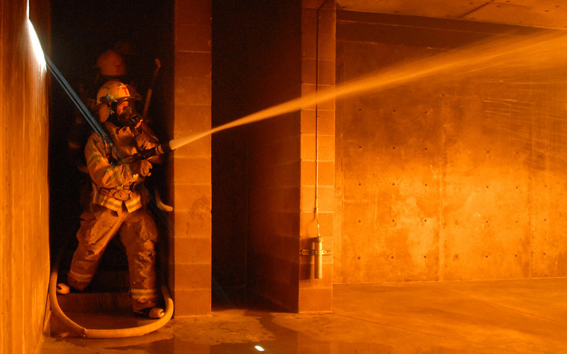 Fire trainees Adam Van Volkinburg begins spraying water as he rounds the corner for fast attack on a live burn basement fire during testing day for the first class to complete their 16-week training at the North Metro Fire Rescue District Training Center on Friday.<br /> <br /> July 9, 2010<br /> Staff photo/ David R. Jennings