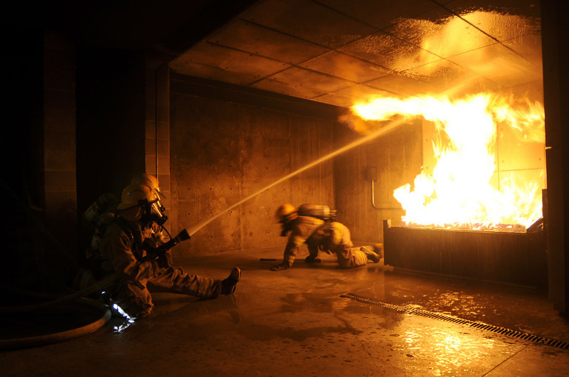 Fire trainees Adam Van Volkinburg and Ryan Ziccarelli use a fast attack to fight a live burn basement fire while Caleb Larson searches the room during testing day for the first class to complete their 16-week training at the North Metro Fire Rescue District Training Center on Friday.<br /> <br /> July 9, 2010<br /> Staff photo/ David R. Jennings