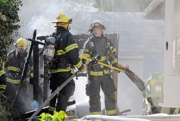 North Metro Fire Rescue firefighters works on opening access to the attic while extinguishing a fire in the 700 block of Kalmia Way on Thursday. No injuries were reported. The cause of the fire is under investigation.<br /> August 11, 2011<br /> staff photo/ David R. Jennings
