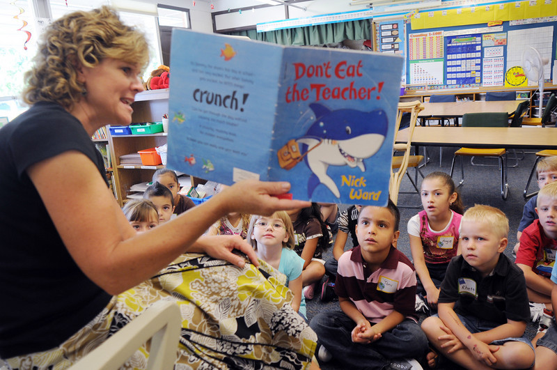 "First grade teacher Valerie Hudson reads the book "" Don't Eat the Teacher "" to her class on the first day of school at Emerald Elementary School on Thursday. Hudson says the first thing she does at the beginning of the school year is read a book and is the last thing she does at the end of the school year.<br /> <br /> August 20, 2009<br /> staff photo/David R. Jennings"